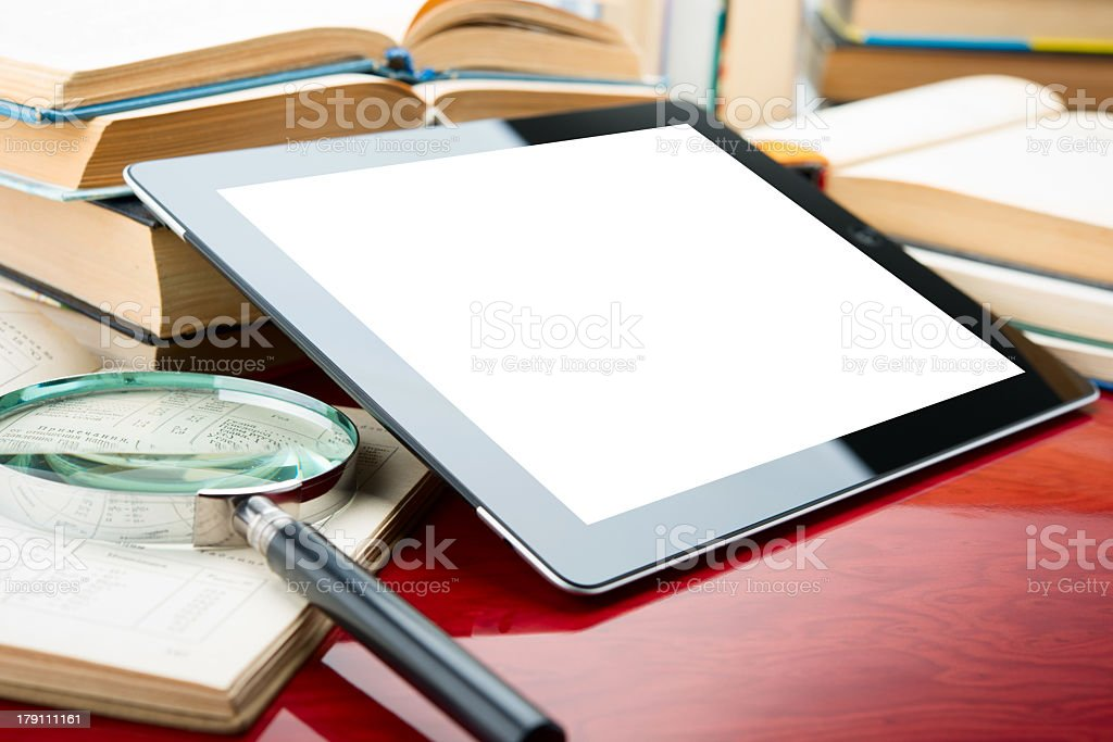 Digital tablet next to magnifying glass and opened books royalty-free stock photo