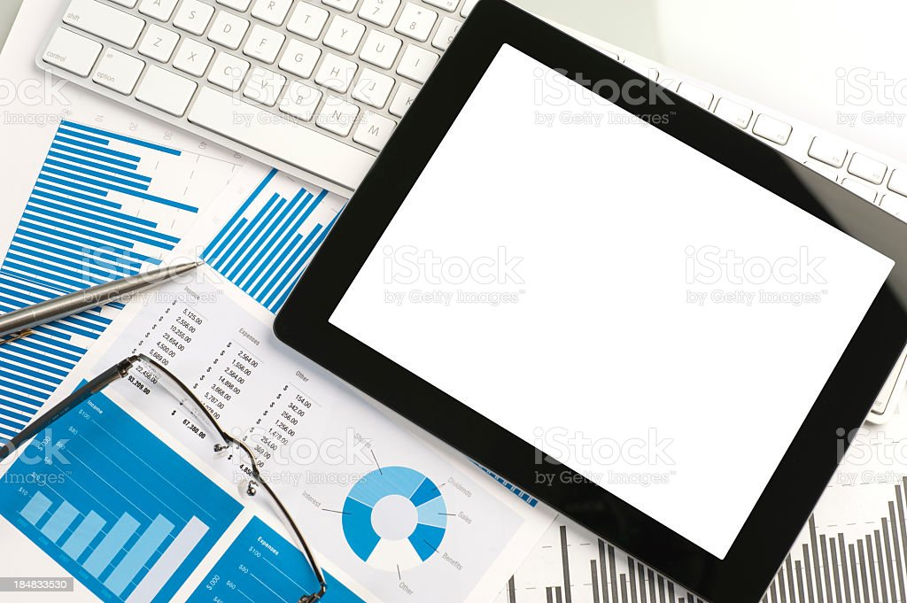 Digital tablet on a desk with financial charts and graphs royalty-free stock photo