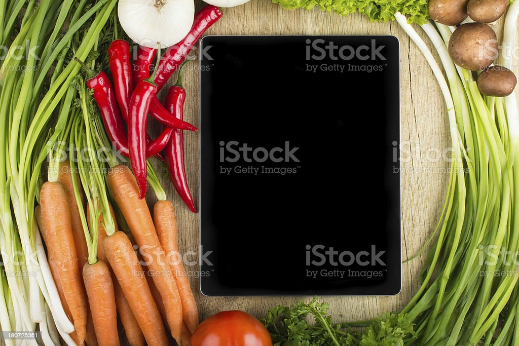Digital tablet on cutting board with fresh vegetables stock photo