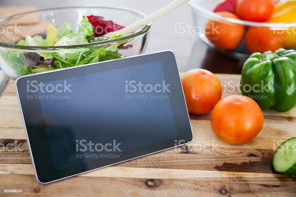 Digital Tablet surround by vegatables. stock photo