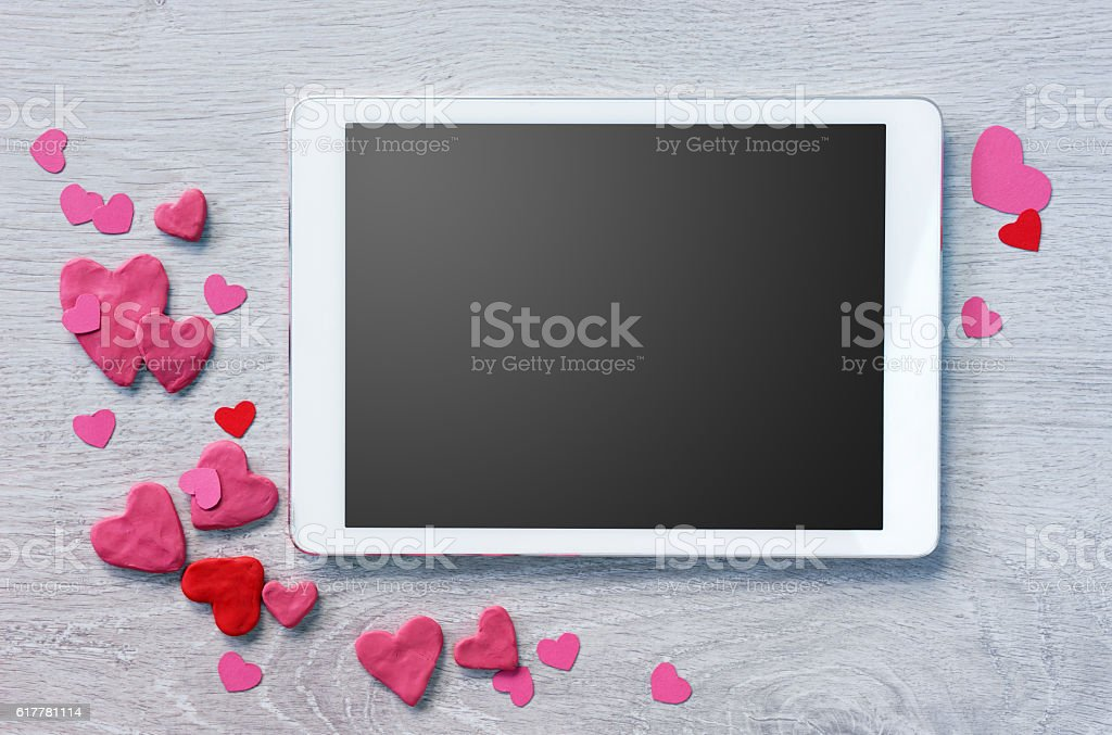 Digital tablet with heap of small hearts stock photo