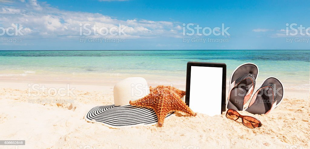 Digital tablet with objects on beach in the Bahamas stock photo