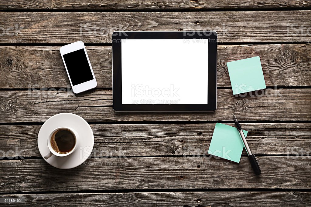 Digital tablet  with sticky notes and coffee on old wood. stock photo