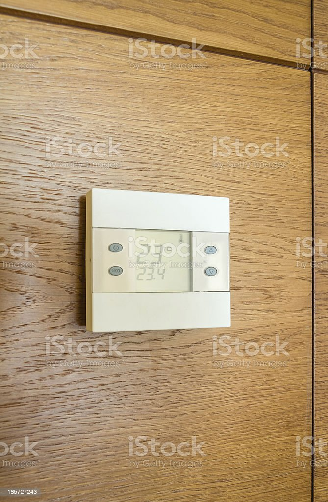 Digital thermostat panel on wooden wall royalty-free stock photo