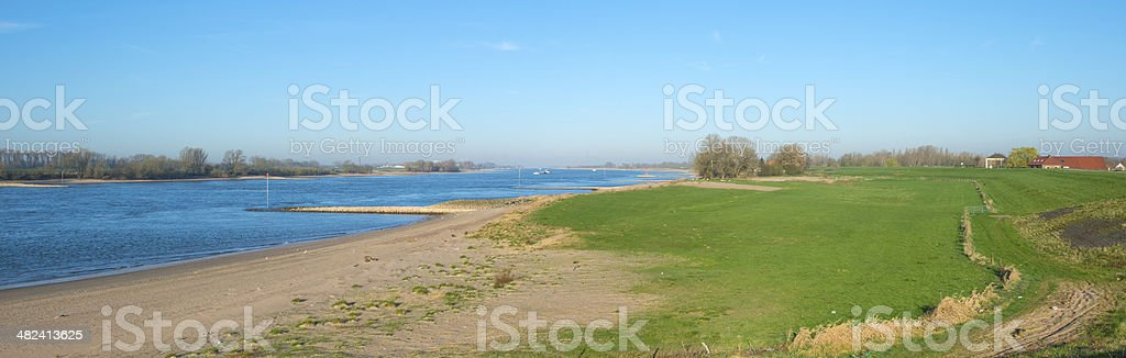 Dike along the shore of a sunny river stock photo