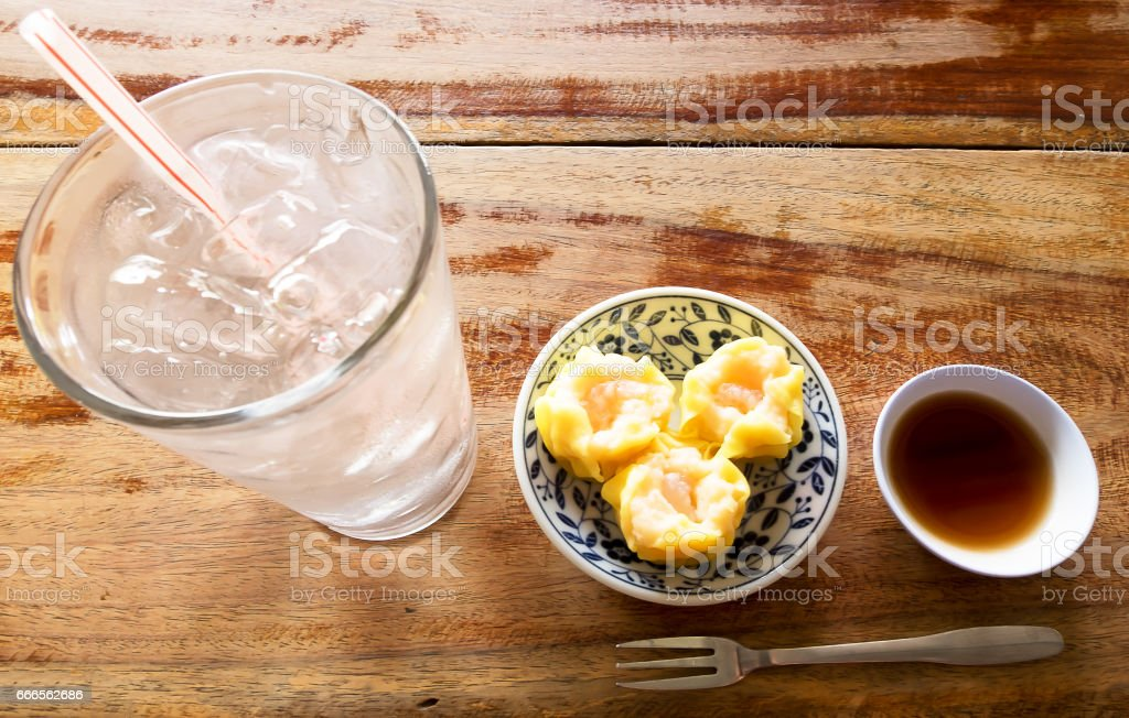 Dim Sum with Soy sauce and Glass of water on wood table stock photo