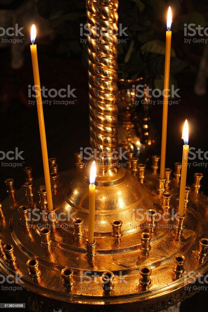 dimly burning church candles stock photo
