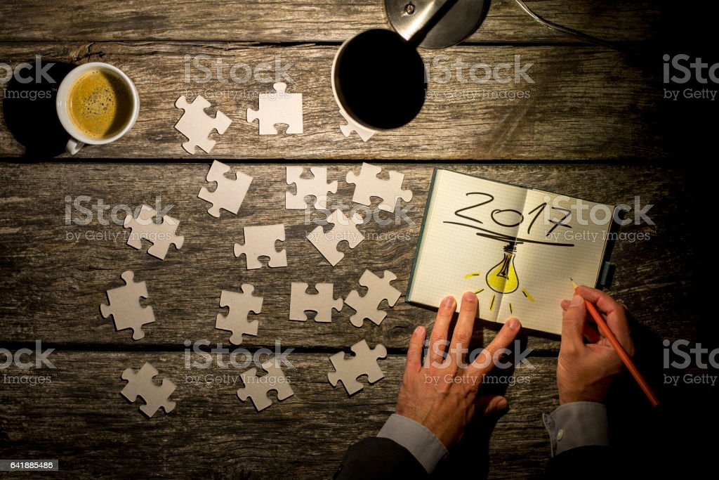 Dimly lit scene of hands writing 2017 with puzzle stock photo