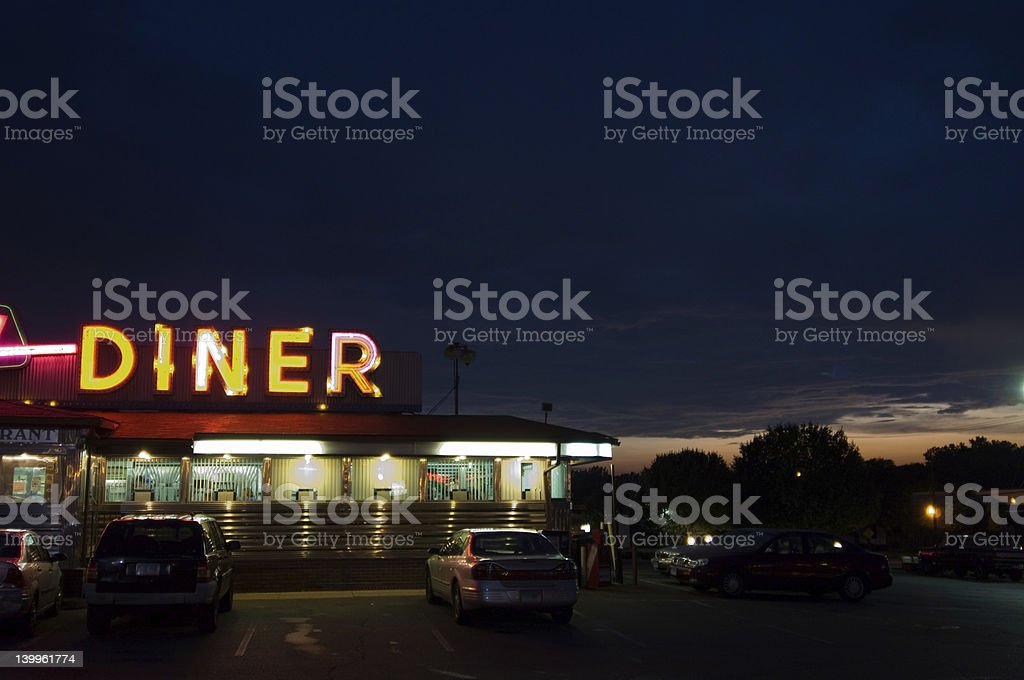 A diner sign lit up at night with cars parked stock photo