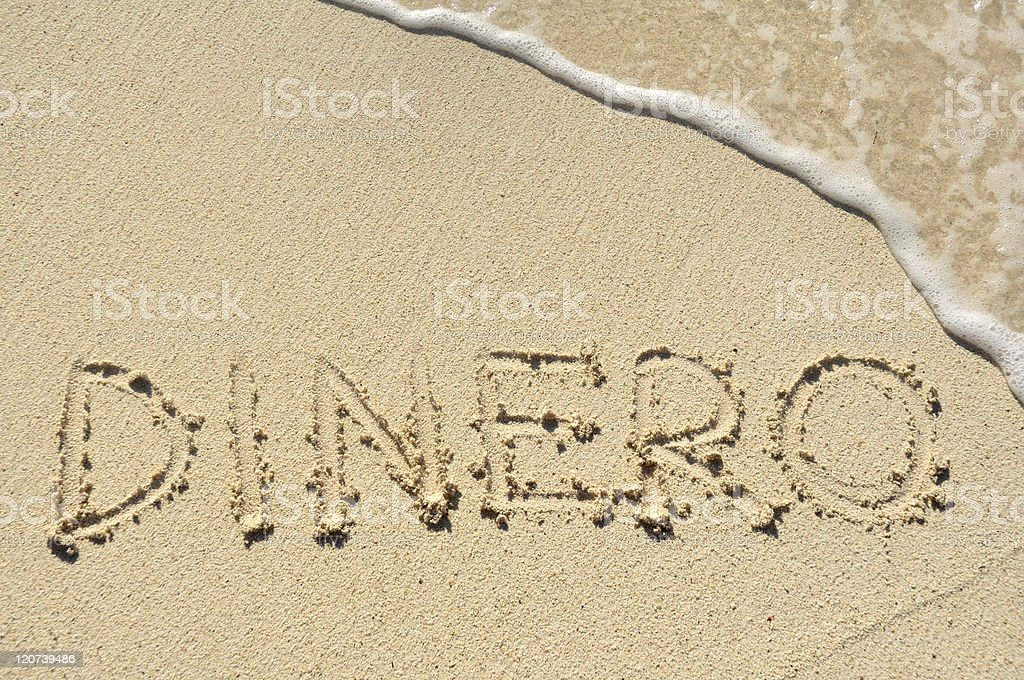 Dinero Written in the Sand on a Beach stock photo
