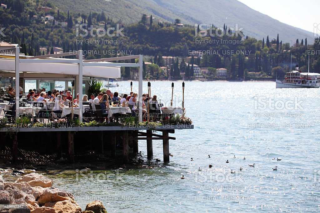 Diners sitting enjoying there food on Lake Garda stock photo