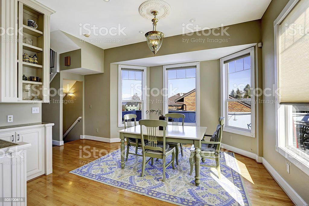Dining room with green wooden table set stock photo