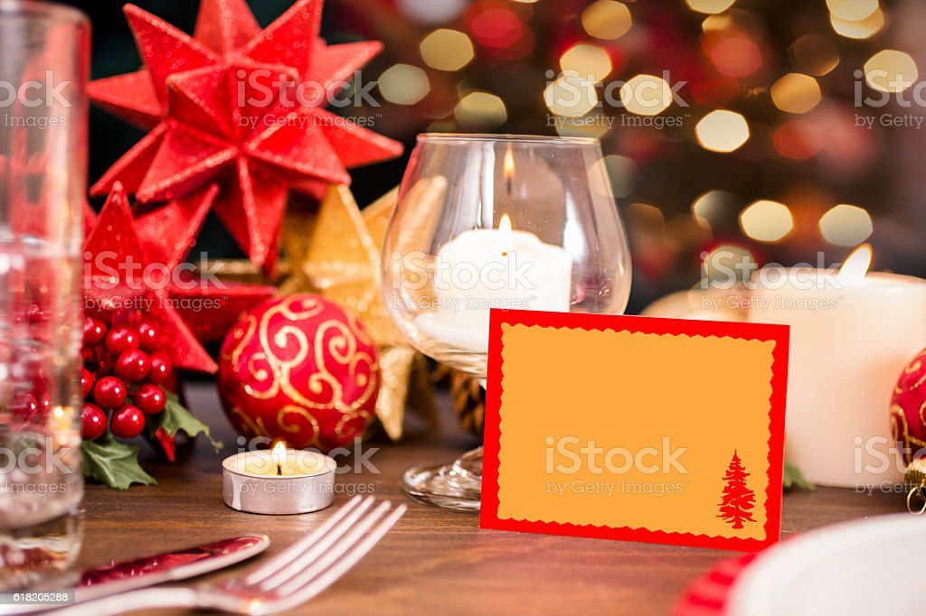 Dining table place setting with Christmas holiday decorations, lights. stock photo