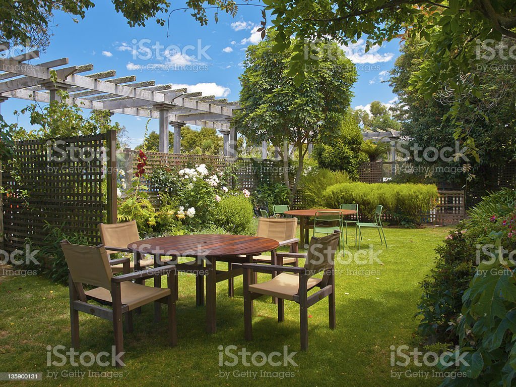 dining table set in lush garden royalty-free stock photo