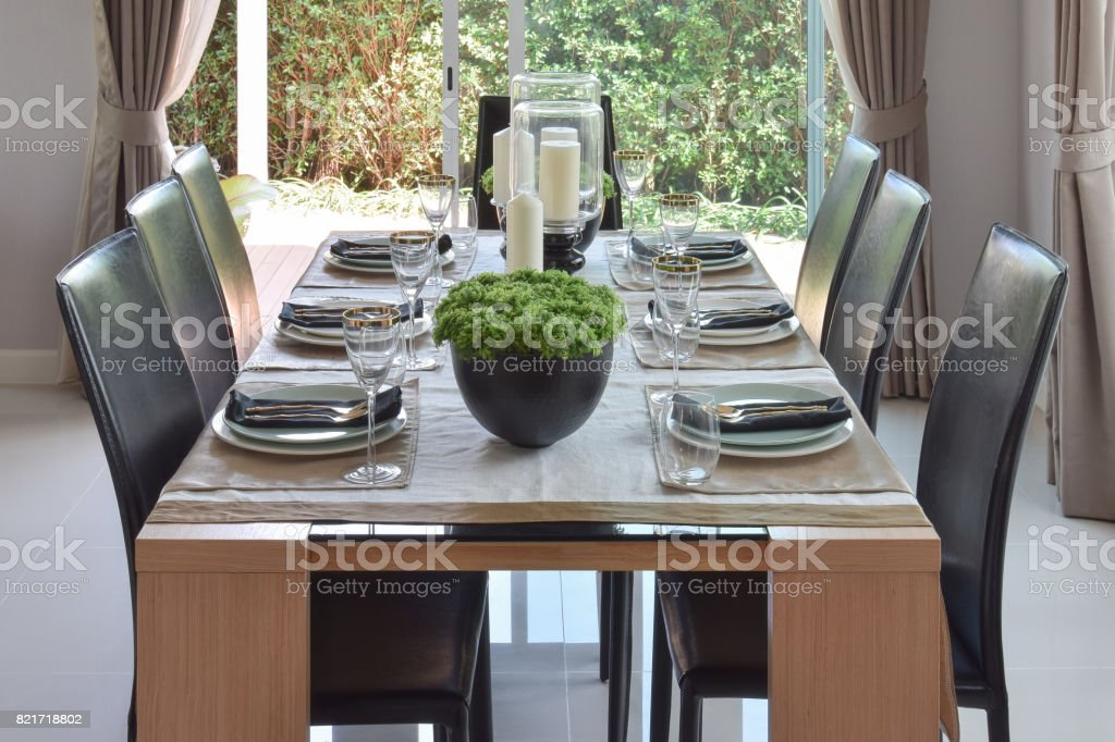 dining wooden table and comfortable chairs in modern home with...