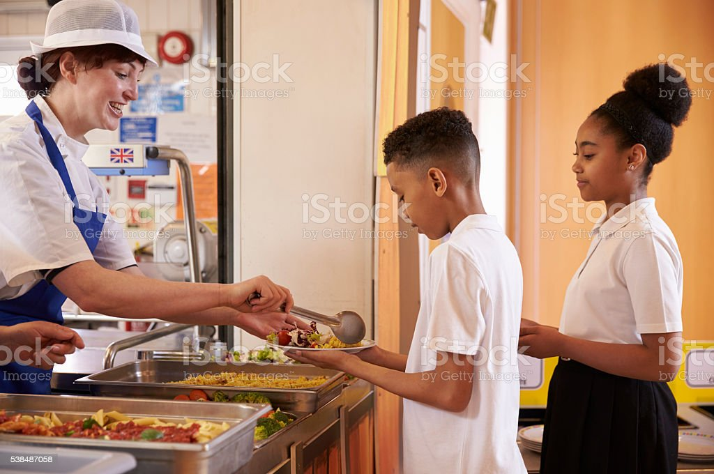 Dinner lady serving kids in a school cafeteria, side view stock photo