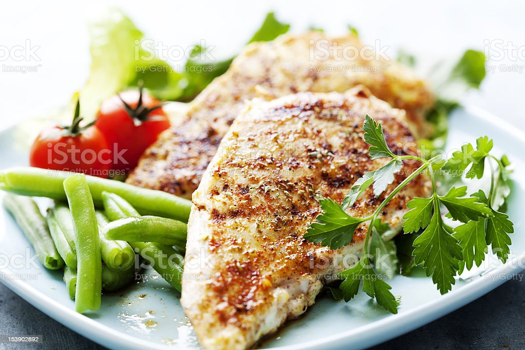 Dinner of grilled chicken breasts, green beans and tomatoes stock photo