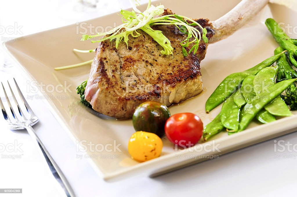 A dinner of veal, snow peas and cherry tomatoes royalty-free stock photo