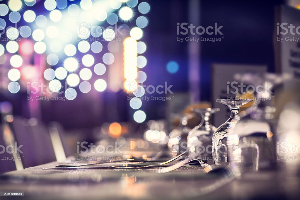 Dinner party table with blurred stage in background with lights stock photo