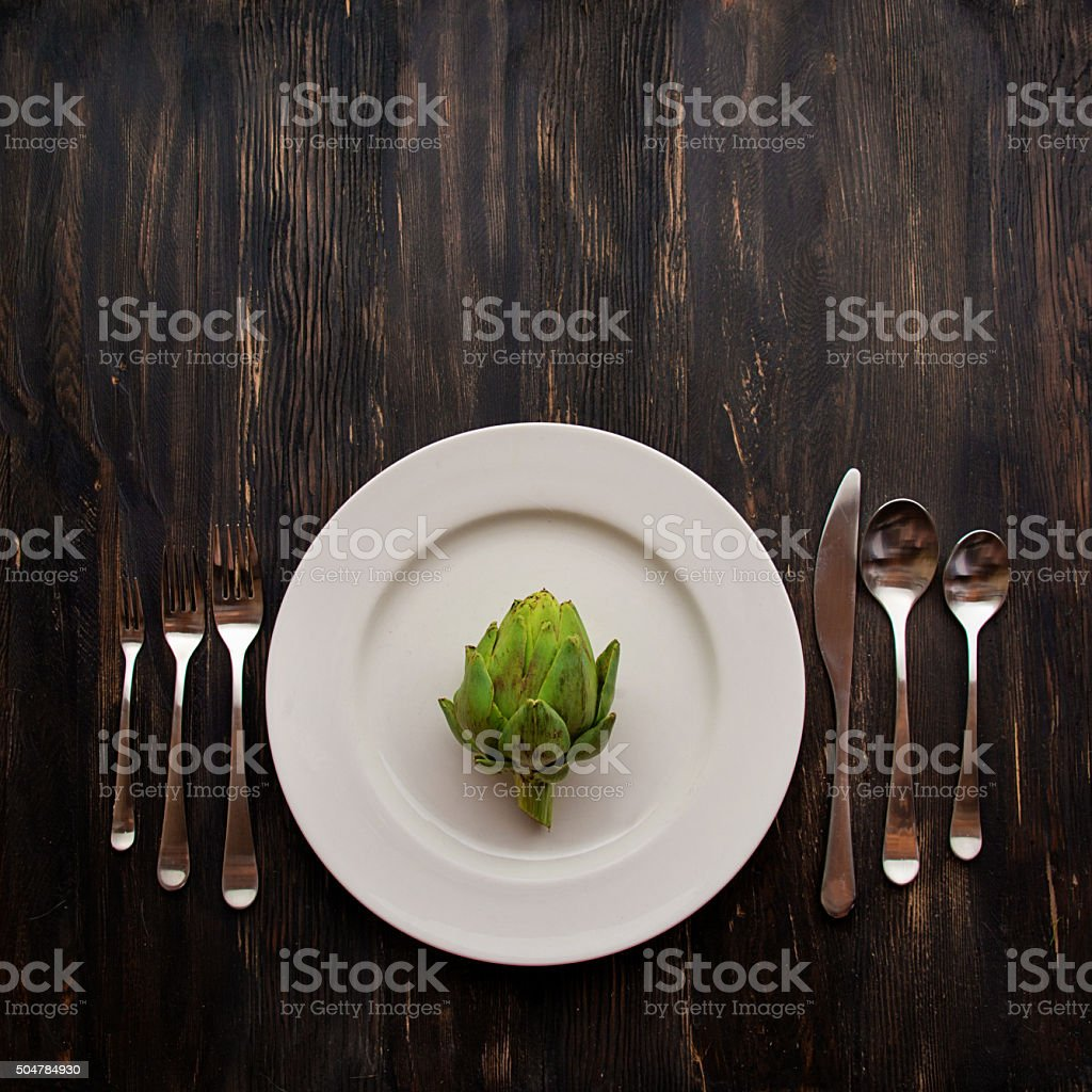 Dinner Plate with Artichoke on Old Wooden Table stock photo
