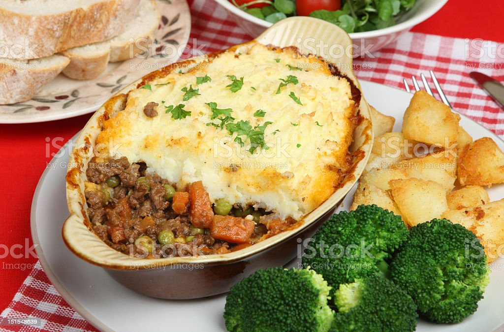 A dinner table with a shepherds pie, broccoli and potatoes stock photo