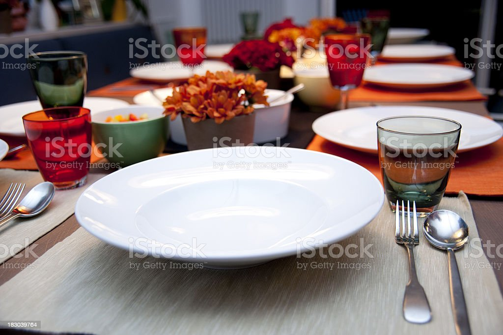 dinner table with empty plates stock photo