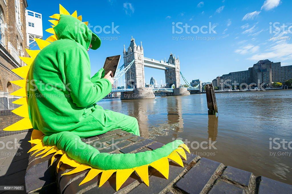 Dinosaur Man Sitting with Tablet in London stock photo