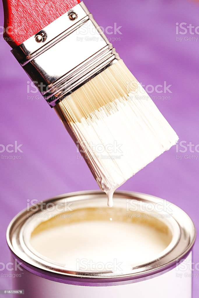Dip brush into the paint stock photo