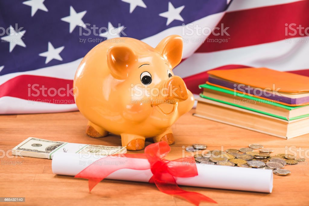 diploma and piggy bank with coins and dollars usa flag behind, education concept stock photo