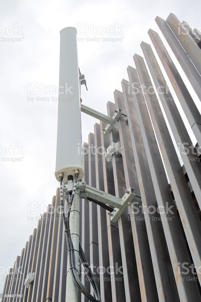 Dipole antenna for telecommunications contrasting white sky back stock photo