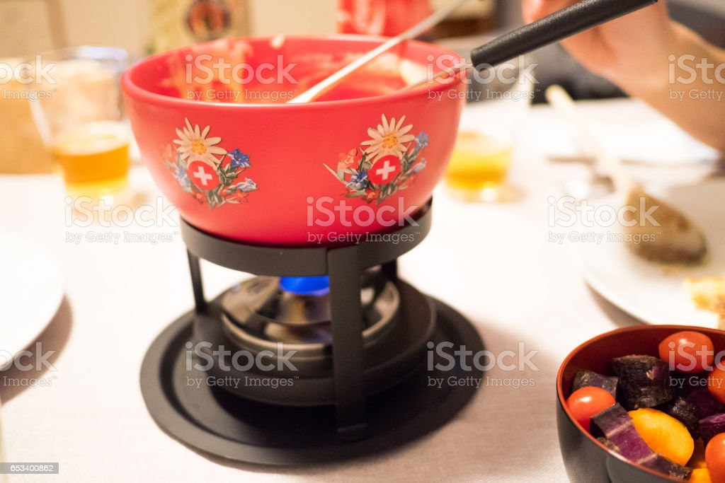 Dipping forks in a red Swiss fondue pot stock photo