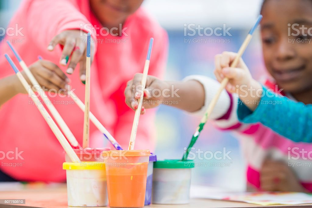 Dipping Paint Brushes in Paint stock photo
