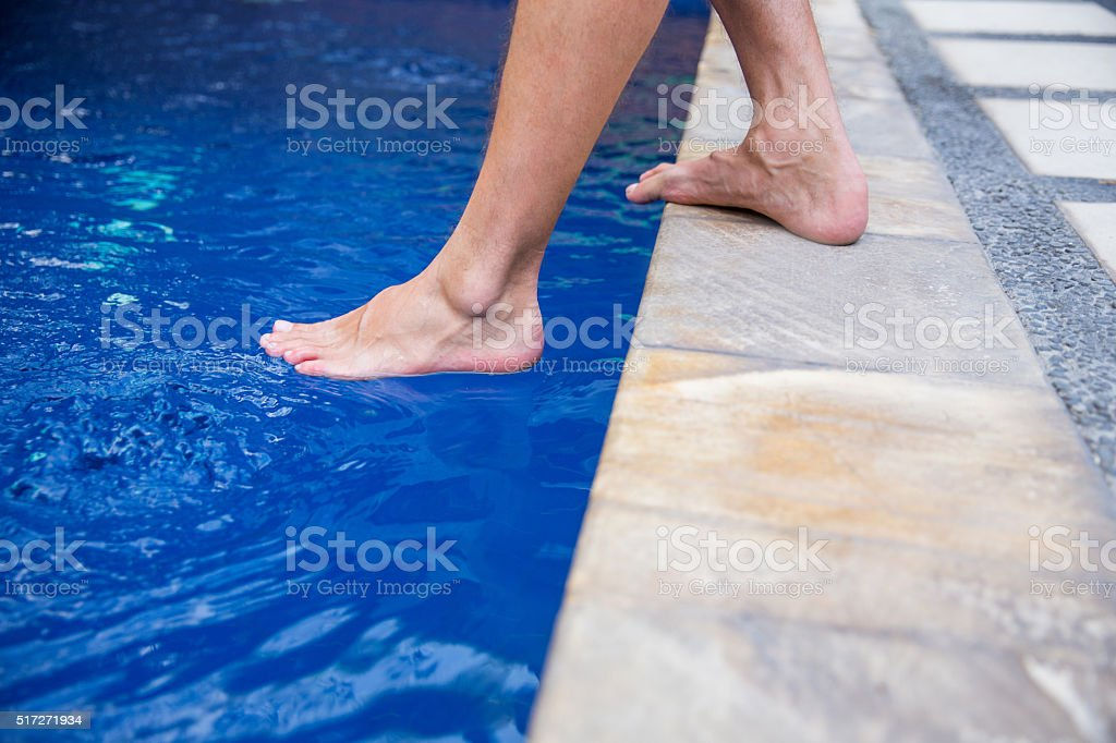 Dipping toe in swimming pool stock photo