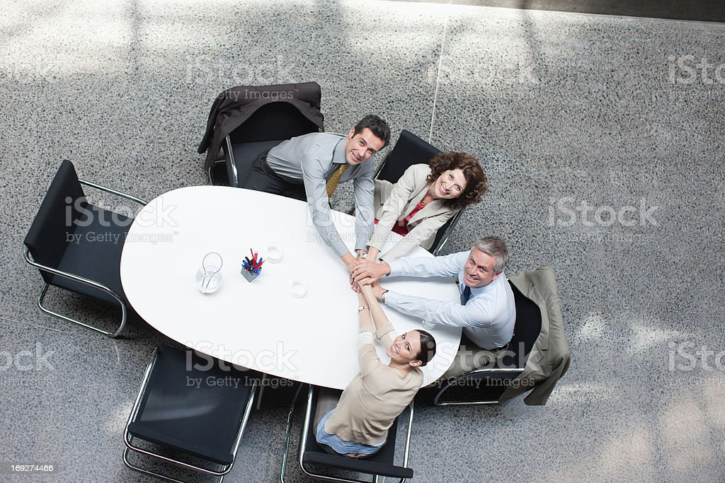 Directly above business people stacking hands at conference table stock photo