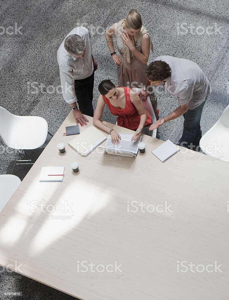 Directly above business people using laptop at conference table stock photo