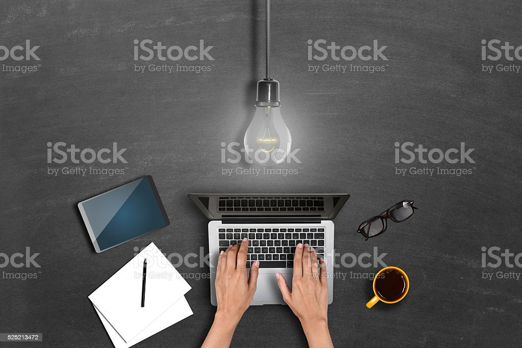 Directly above of a man's hand using laptop with lightbulb stock photo