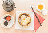 Directly above table view of steaming basket with dim sum