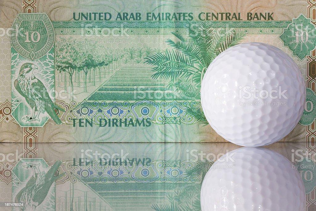 Dirhams and golf ball stock photo