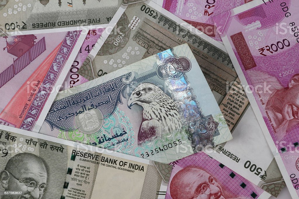 UAE Dirhams between Indian New Currency Bank Notes stock photo