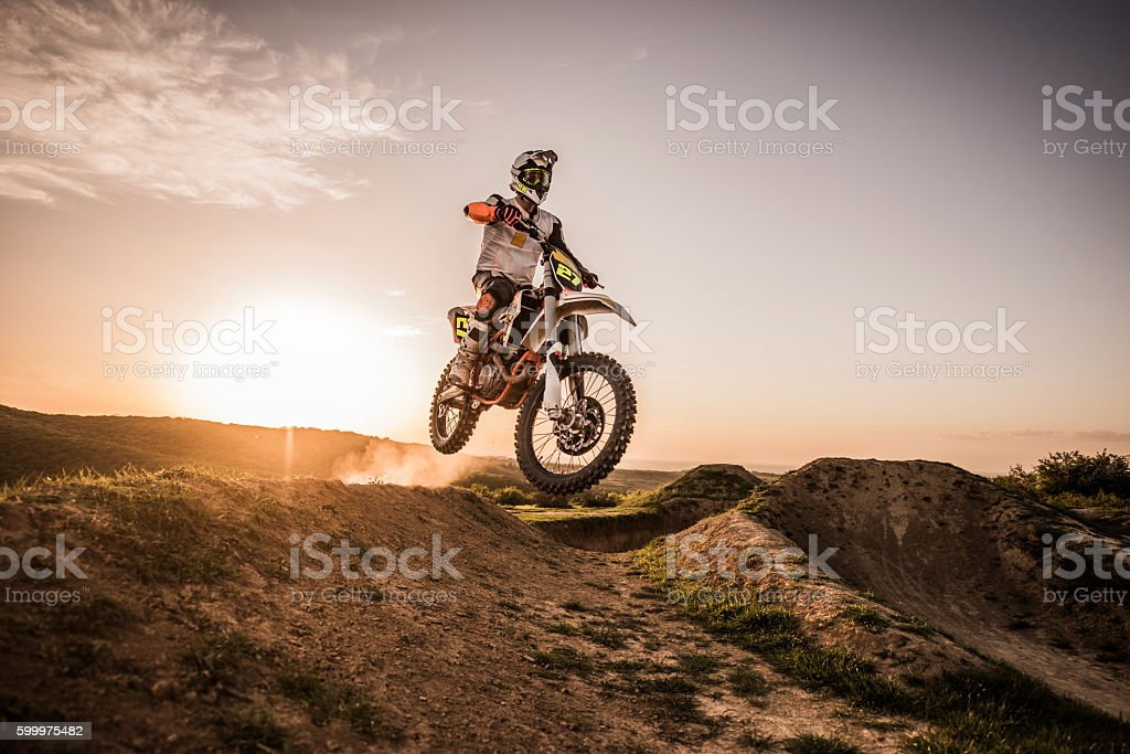 Dirt bike racer at sunset performing jump on dirt road. stock photo