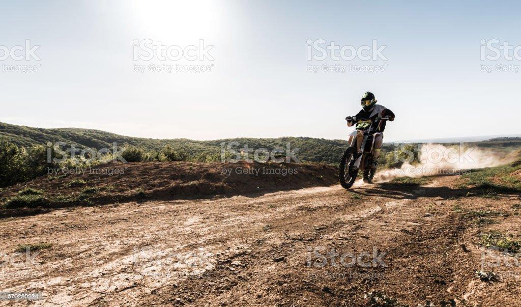 Motocross bike rider racing on dusty road. Copy space.