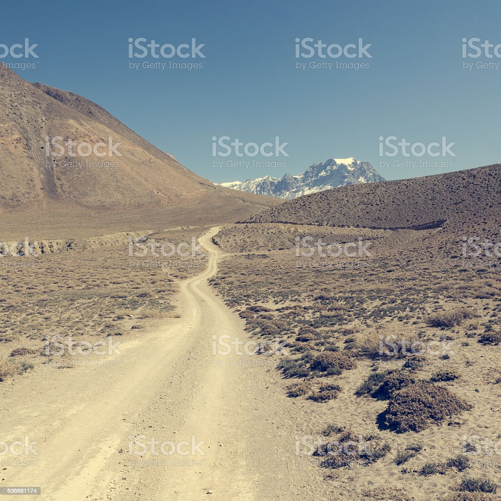 Dirt road through arid mountain wastelands. stock photo