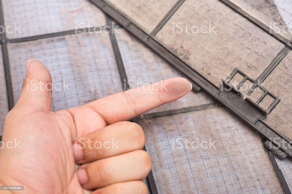 dirty air conditioner filter and dirty finger stock photo