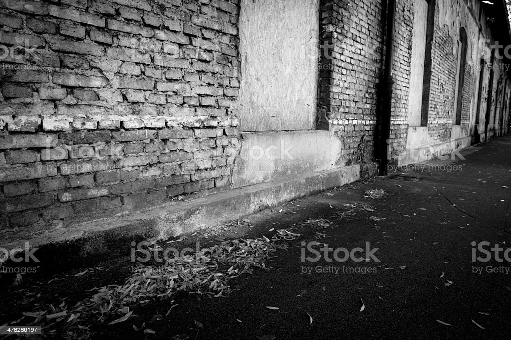 dirty alley with a brick wall royalty-free stock photo