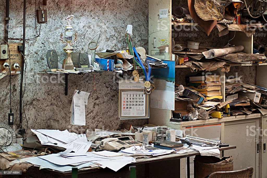 dirty and abandoned office with books and papers stock photo