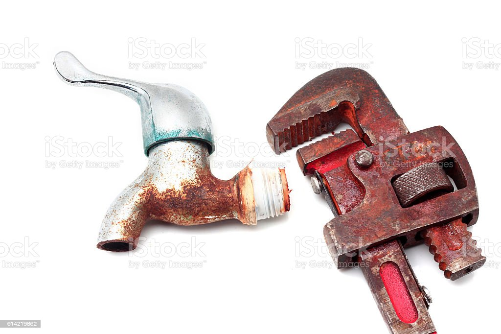 Dirty and rusty pipe wrench with taps stock photo