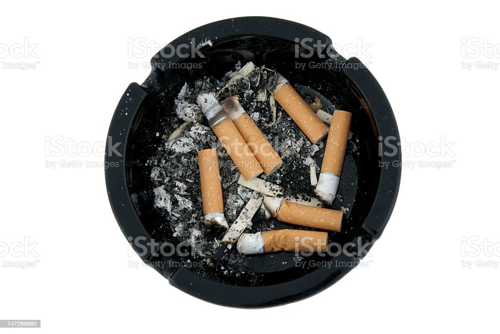 Dirty ashtray full of smoked cigarette butts royalty-free stock photo