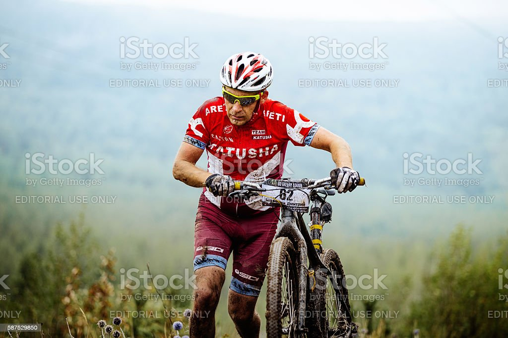 dirty athlete mountainbiker uphill walk with their bikes royalty-free 스톡 사진