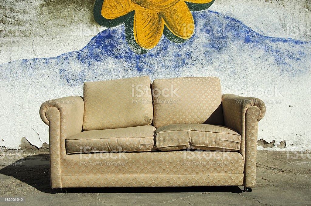 Dirty brown couch on sidewalk with mural in background  royalty-free stock photo