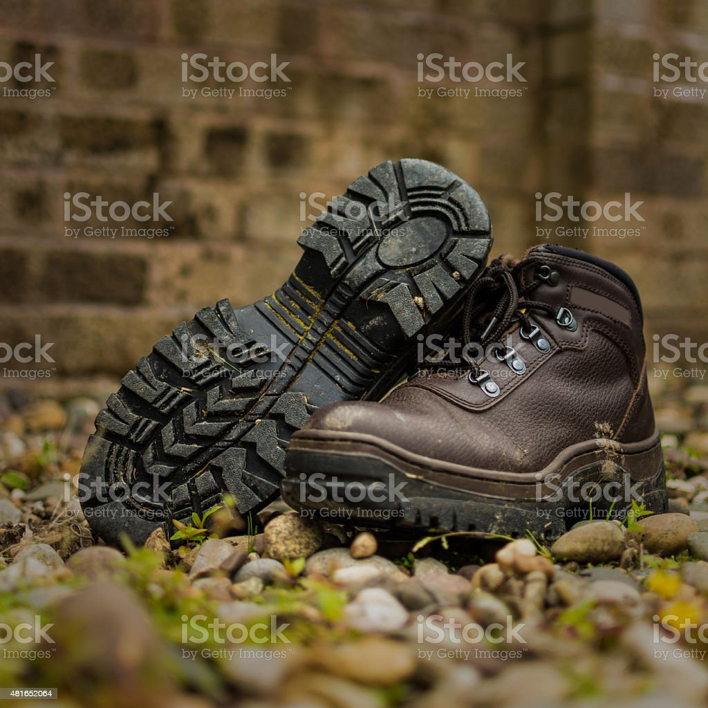 Dirty Brown Leather Walking Boots On Pebble Outdoors Background. stock photo